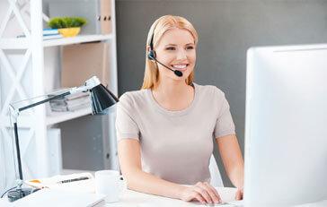 Eine junge lächelnde Dame mit Headset die vor einem PC sitzt